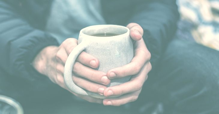 a man holding his cup of coffee