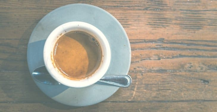 a brown coffee in a cup on a wooden table