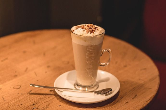 a glass of latte with whipped cream