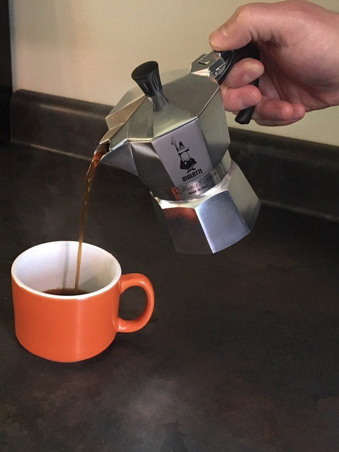 pouring coffee from a bialetti moka pot