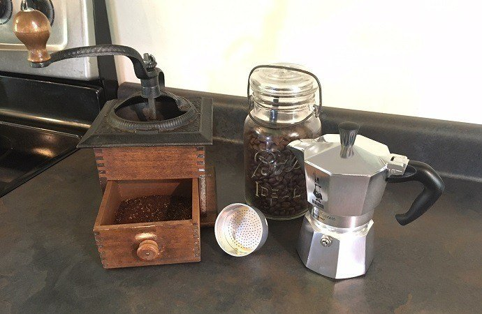 a hand grinder, a coffee bean container, and a stovetop coffee maker
