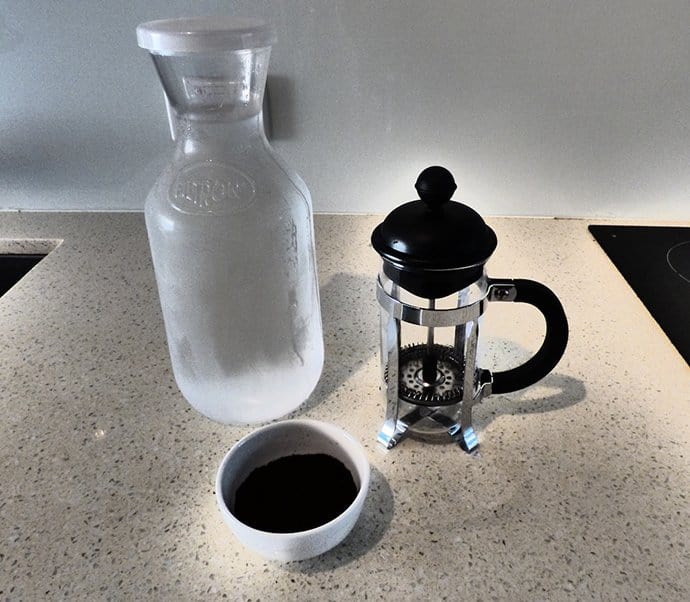 Glass jug of water, french press and coffee grounds