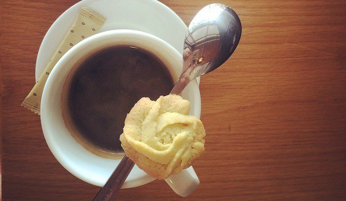 a cup of americano coffee with biscuit