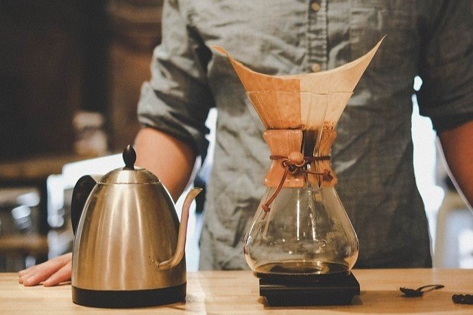 kettle for making hot water, chemex carafe, and coffee filter in front of a guy