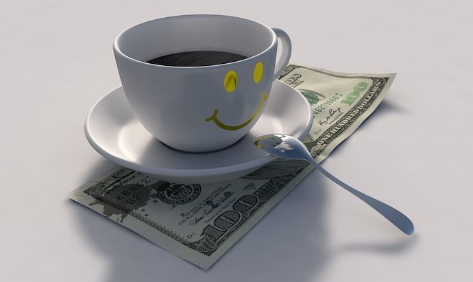 Coffee cup sitting on a one hundred dollar bill