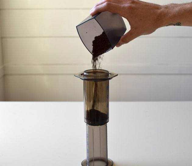 Pouring ground coffee in a coffee maker