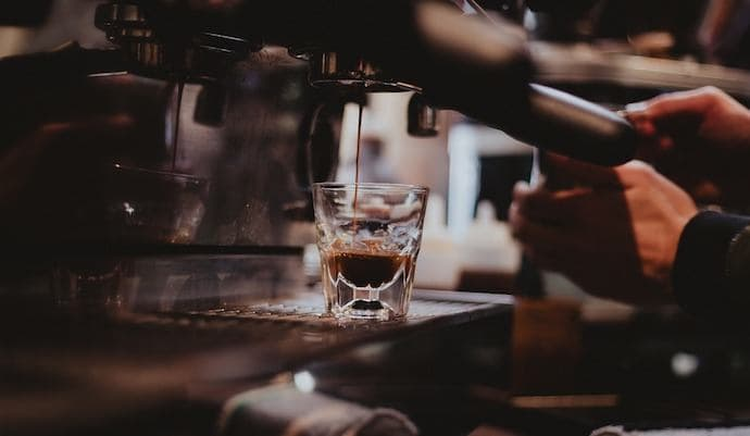 a shot of espresso pouring from espresso machine