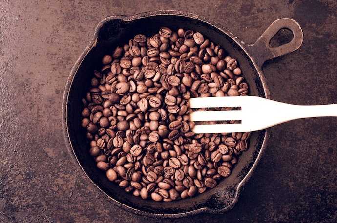 roasting coffee beans in a pan