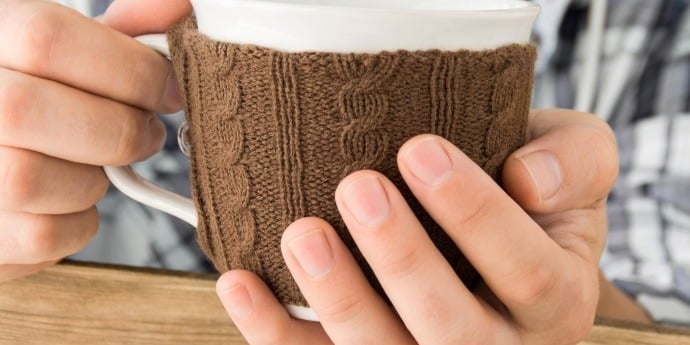 Cup of coffee in cup sleeve to keep it hot