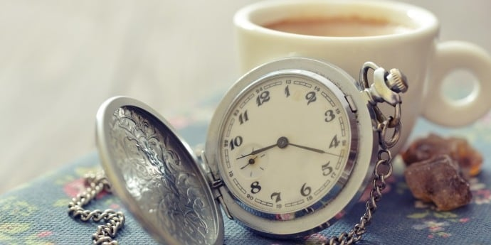 a pocket watch and a cup of coffee on a table