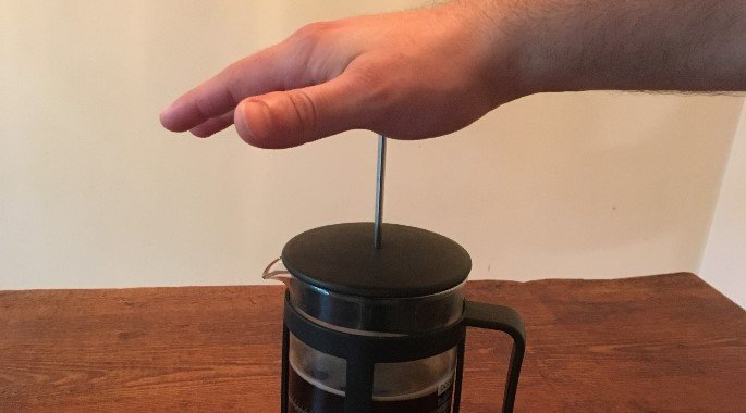 pushing the metal stick into the pot to make French Press coffee