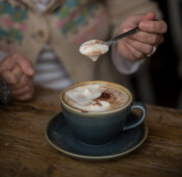 a person showing the froth of a bone dry cappuccino