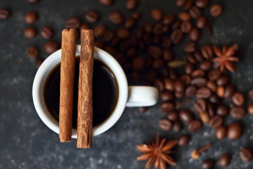 A cup of coffee with a cinnamon stick above it.