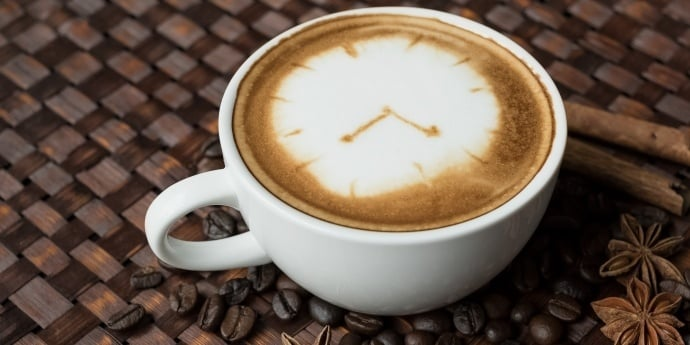 a cup of latte with a clock as art - clearly not a clean cup of coffee