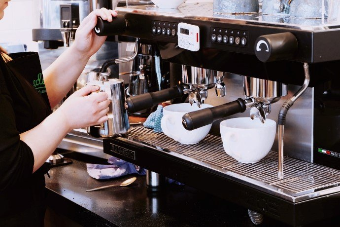 a barista steaming milk using a commercial espresso machine