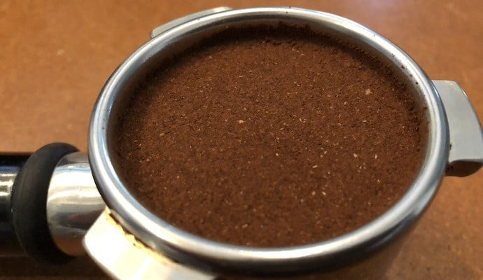 flat bed of coffee grounds in a portafilter
