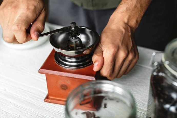 man grinding coffee beans with a manual grinder
