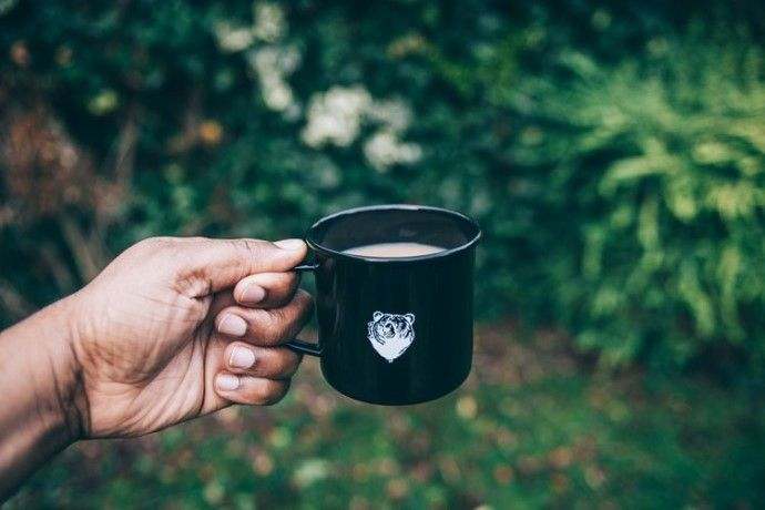 a cup of coffee being held outdoors