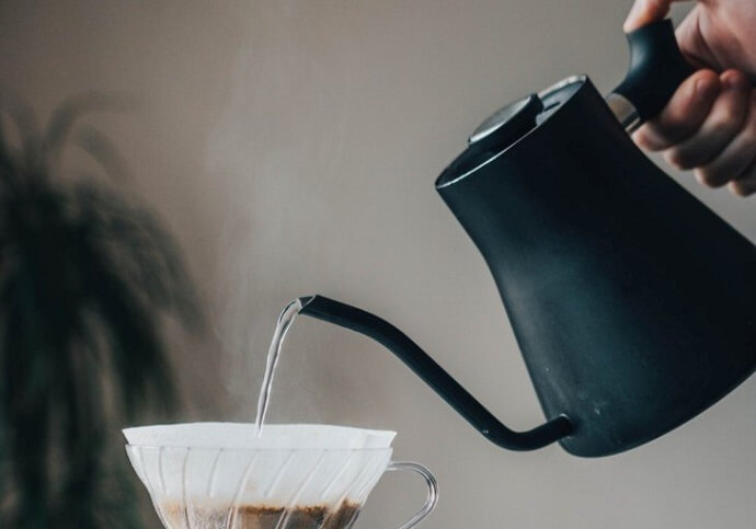 a fellow stagg gooseneck kettle pouring into a coffee maker