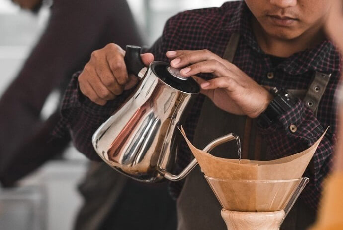 a man using a gooseneck kettle that looks like a willow and everett kettle for making pour over coffee