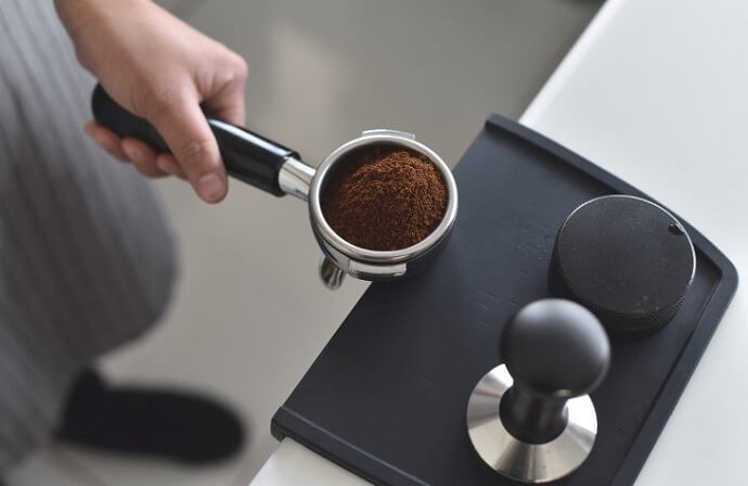 espro calibrated tamper review - a portafilter filled with espresso grounds, a tamper