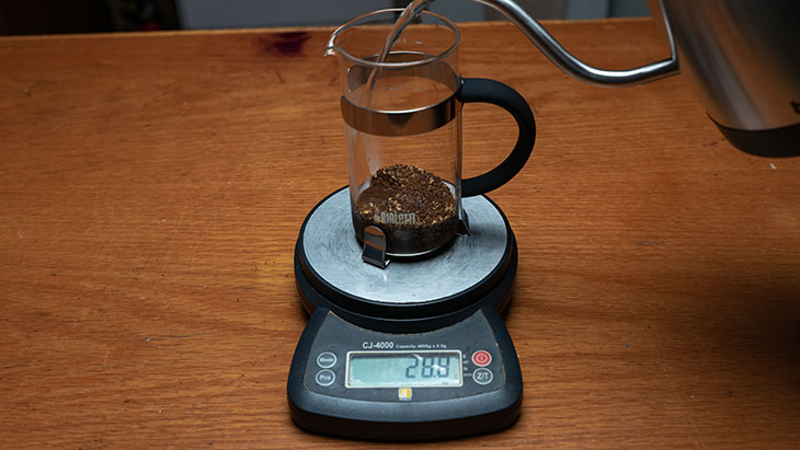 pouring coffee into a french press on scales