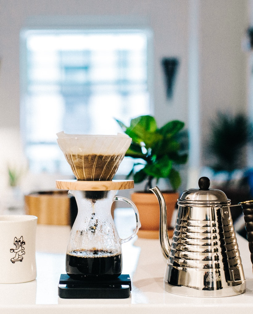 a dripper with coarse ground coffee in it, a carafe, and a kettle with hot water
